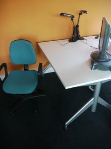 Ein (noch) leerer Platz. Netzstecker, Zusatzmonitor und Bürostuhl warten auf ihre Erfüllung. Eigentlich sind die Sessel auch personalisiert, aber irgendwie macht sich keiner die Mühe, den eigenen Sitzplatz zu hüten.